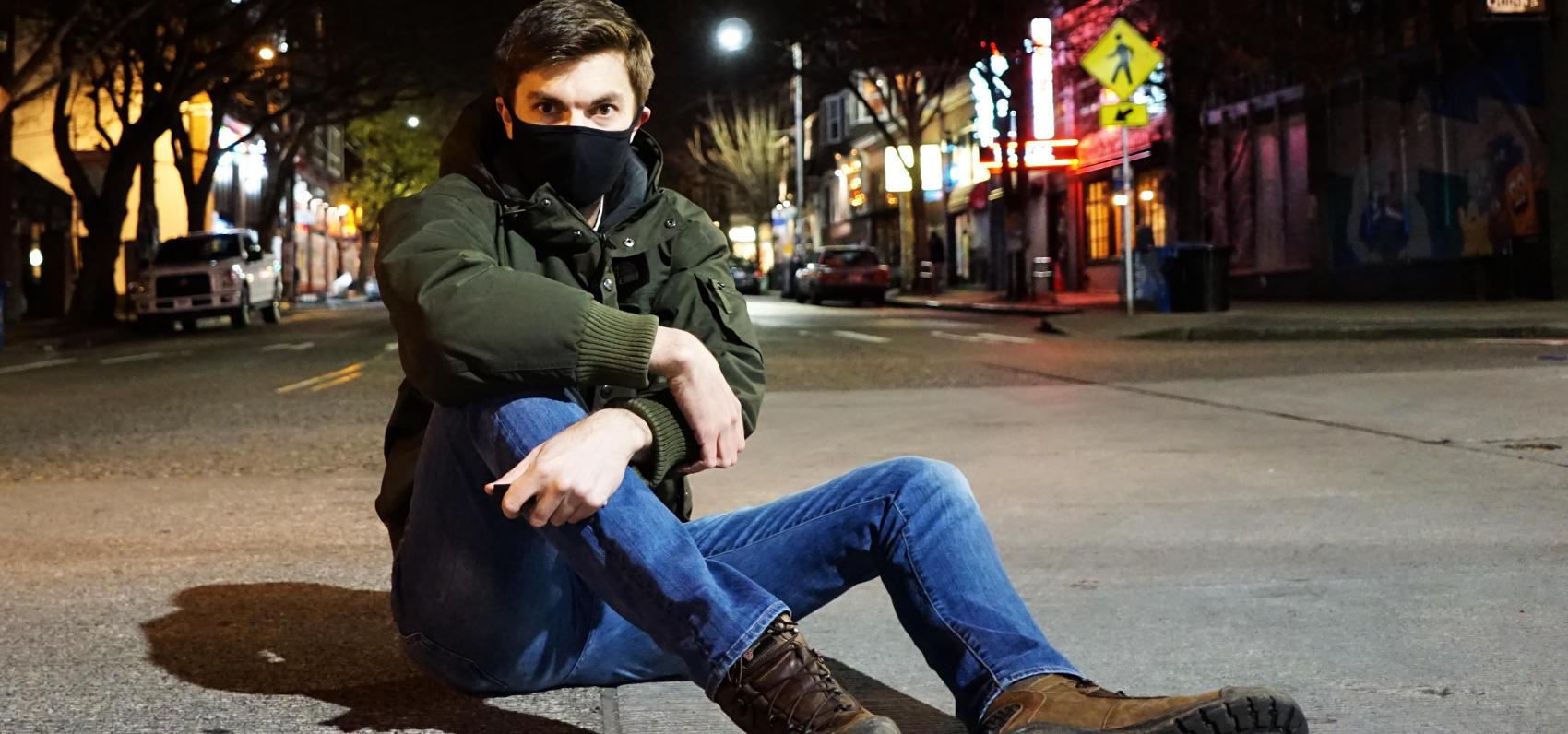 A photograph of Gaelan Lloyd sitting in a deserted street at night