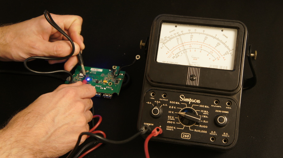 A person using an electronic voltage measuring tool